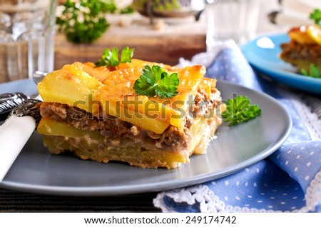 Portion of graten potatoes and minced meat on a ceramic plate - stock photo