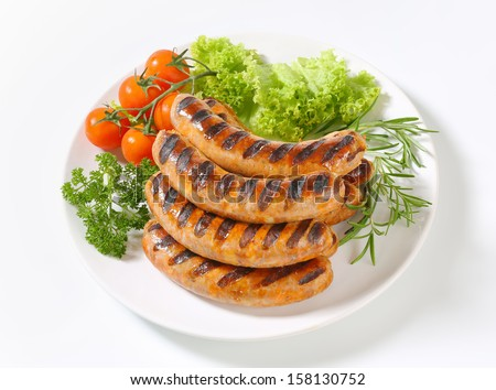 portion of grilled sausages served with vegetable side dish, on a plate - stock photo