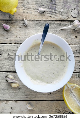 Portion of homemade Aioli dip in small soup plate on wooden background. Fresh aioli sauce with spoon in it and garlic with lemon around it. - stock photo