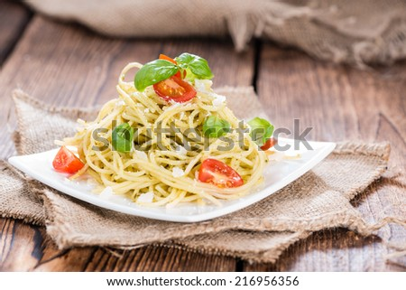 Portion of Italian food (Spaghetti with Pesto, Parmesan Cheese and Tomatoes)
