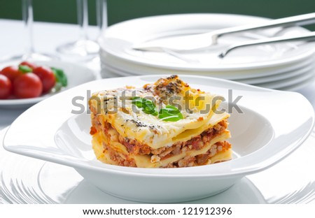 Portion of lasagna with meat topped with parmesan