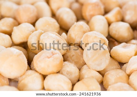 Portion of Macadamia nuts (roasted and salted) for use as background image or as texture - stock photo