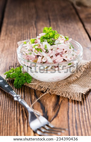 Portion of Meat Salad (made with mayonnaise) on wooden background - stock photo