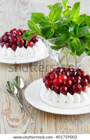 Portion of meringue cake with cream and cranberries. Fresh mint in a glass
