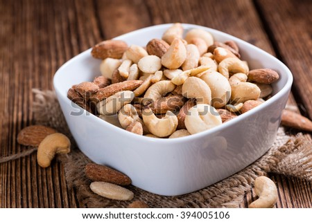 Portion of mixed nuts (roasted and salted) on an old wooden table (selective focus) - stock photo