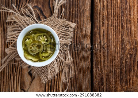 Portion of preserved Jalapenos (close-up shot) on wooden background - stock photo