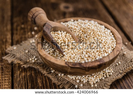 Portion of puffed Quinoa (selective focus; detailed close-up shot) on an old wooden table - stock photo