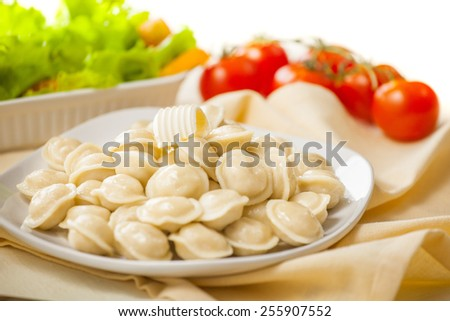 Portion of ravioli on a white plate. Green salad and tomatoes. - stock photo
