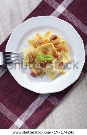 Portion of ravioli with onion and bacon on white plate - stock photo