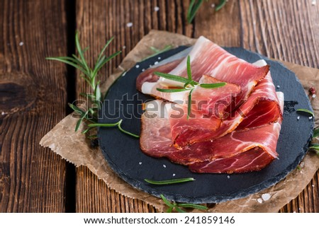 Portion of sliced smoked Ham with fresh herbs on wooden background - stock photo