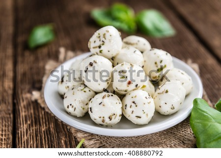 Portion of small Mozzarella Cheese (marinated with herbs; selective focus) - stock photo