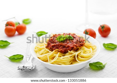 Portion of spaghetti bolognese with basil leaves and tomatoes - stock photo