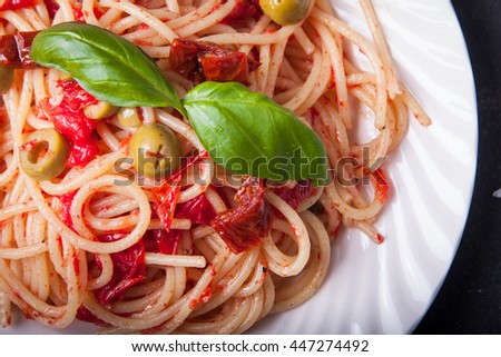 Portion of spaghetti with sun dried tomatoes, garlic, basil, olives and olive oil - stock photo