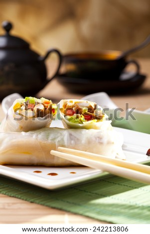 Portion of spring rolls on plate with dipping sauce - stock photo