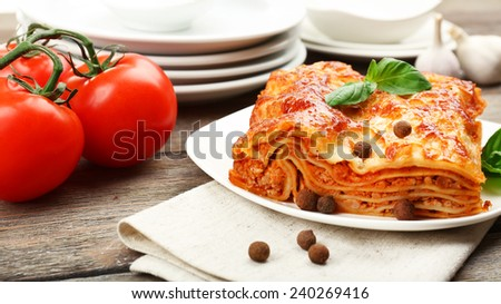 Portion of tasty lasagna on wooden table - stock photo