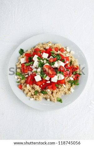 Portion of tomato quinoa salad with red pepper and spinach - stock photo