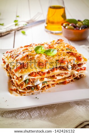 Portion of traditional durum wheat lasagne with bolognaise sauce, beef mince and cheese in alternating layers on a white plate - stock photo