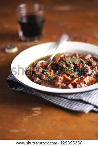 Portion of traditional irish beef and guinness beer stew with carrots and fresh parsley in a plate ready to serve - stock photo