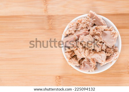 Portion of Tuna with fresh parsly on wooden background - stock photo