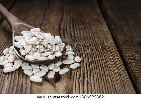 Portion of white beans (close-up shot) on rustic wooden background - stock photo