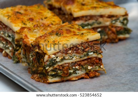Portioned Pieces of baked spinach and beef lasagna ready for serving