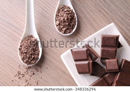 Portions and chocolate chips on a white porcelain container on a brown wooden table. Horizontal composition. Top view - stock photo
