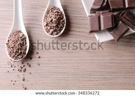 Portions and chocolate chips on a white porcelain container on a brown wooden table. With space for writing. Horizontal composition. Top view - stock photo