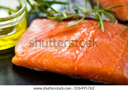 Portions of Fresh Raw Salmon Fillets with Aromatic Herbs and Spices and Olive Oil , Shallow DOF, Selective Focus - stock photo