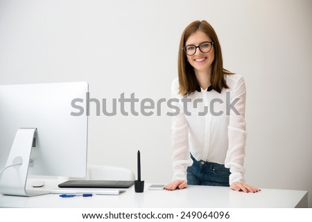Portirrait of a beautiful smiling businesswoman standing near her workplace - stock photo
