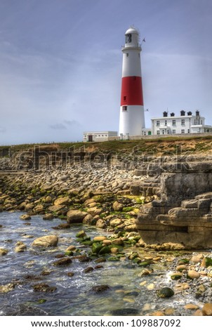 Portland Bill lighthouse, Dorset, England, with rocks at low tide, HDR - stock photo