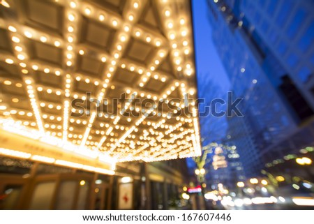 Portland Oregon Downtown Broadway Entertainment and Shopping District at Evening Blue Hour with Marquee and Traffic Lights Blurred Bokeh Background - stock photo