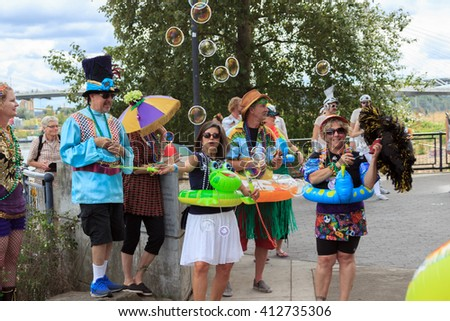Portland, Oregon, USA - July 26, 2015: The Big Float 2015 - Parade goers blow bubbles as the other begin the procession down to the water during the Big Float 2015