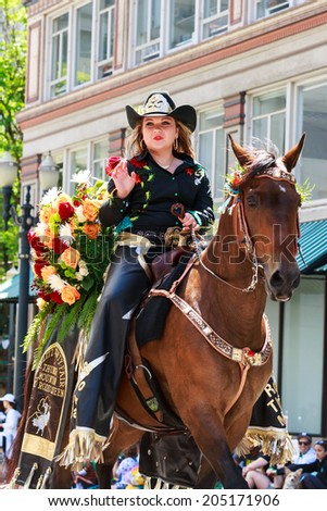 Portland, Oregon, USA - JUNE 7, 2014: Miss Thunder Mountain Pro Rodeo Queen, Brianna Howell in Grand floral parade through Portland downtown.