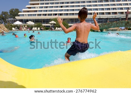 PORTO KARRAS, CHALKIDIKI- JULY 29, 2014: Visitors jumping in to the pool, having fun on a hot day in summer in Chalkidiki, Greece.