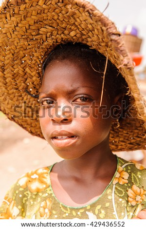 PORTO-NOVO, BENIN - MAR 9, 2012: Unidentified Beninese  beautiful girl in a straw hat. People of Benin suffer of poverty due to the difficult economic situation.