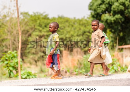 PORTO-NOVO, BENIN - MAR 8, 2012: Unidentified Beninese children run in the street. People of Benin suffer of poverty due to the difficult economic situation.