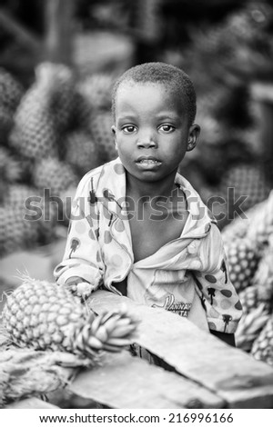 PORTO-NOVO, BENIN - MAR 8, 2012: Unidentified Beninese little boy in a Hanna Montana shirt. People of Benin suffer of poverty due to the difficult economic situation. - stock photo