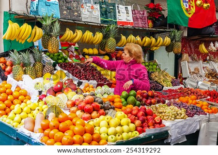 Porto, Portugal. December 29, 2014: Fruit seller organizing and taking care of the stand in the interior of the historical Bolhao Market - stock photo