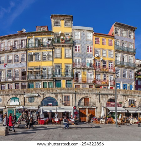 Porto, Portugal. December 29, 2014: The typical colorful buildings of the Ribeira District with the popular shops, restaurants and bars built in the stone wall. Unesco World Heritage Site. - stock photo
