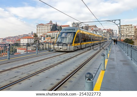 Porto, Portugal. January 5, 2015: Porto Subway train passes by the superior deck of the Dom Luis I bridge connecting Gaia to the city of Porto, seen in the background, over the Douro River. Portugal - stock photo