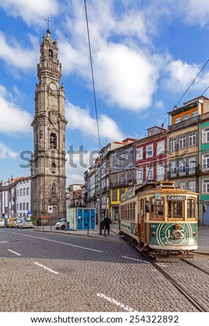 Porto, Portugal. January 5, 2015: The old tram passes by the Clerigos Tower, one of the landmarks and symbols of the city. Unesco World Heritage Site - stock photo