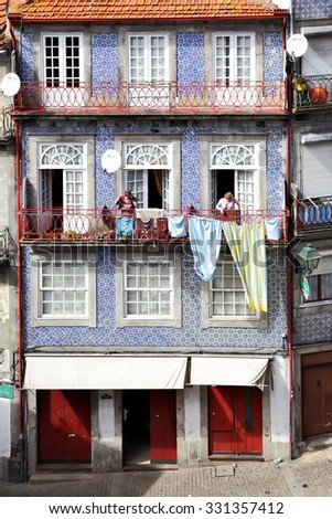 PORTO, PORTUGAL - May 12, 2012: Unidentified women dry linen on the balcony of traditional house in Porto
