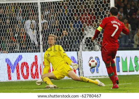 PORTO, PORTUGAL - OCTOBER 8: Cristiano Ronaldo (POR) scores Portugal 3rd goal in front of helpless goalkeeeper Anders Lindegaard (DEN) in Euro2012 Qualifying match on October 8, 2010 in Porto, Portugal - stock photo