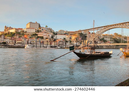 "Porto, Portugal: sunset view of iconic Dom Luis bridge and the Ribeira historical quarter, over Douro river, with some ""rabelos"" (traditional wine cargo boats). Unesco World Heritage."
