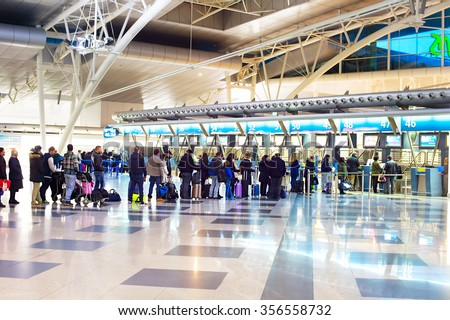 PORTO, PORUTGAL - JAN 16, 2015: People waiting in queue at a check-in counter in Francisco Sa Carneiro Airport. The airport was originally built in the 1940s  - stock photo