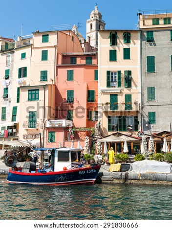 PORTOVENERE, ITALY - APRIL  27;12th century Italian harbor promenade along  pedestrian only zone lined tall colorful houses, seafood restaurants, fishing boat on April, 27, 2011, in Portovenere Italy. - stock photo