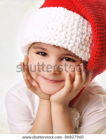 Portrai of happy smiling beautiful little boy in hat of Santa Claus, retro style - stock photo