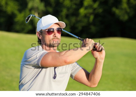Portrain of man in sunglasses on sunny green golf course. Golfer with white hat on shooting a golf ball. - stock photo