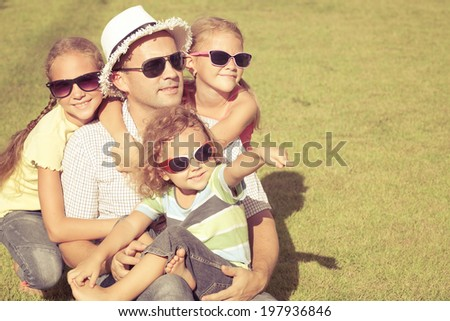 Portrait a happy family sitting on the grass at the day time - stock photo