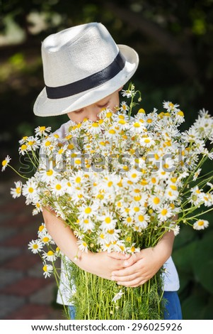 Portrait adorable boy in a hat with big white bouquet of camomiles. Summertime. - stock photo